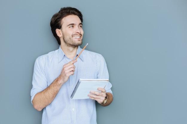 Jonge schrijver. gelukkig positieve aardige man die zijn notitieboekje vasthoudt en lacht terwijl hij inspiratie voelt