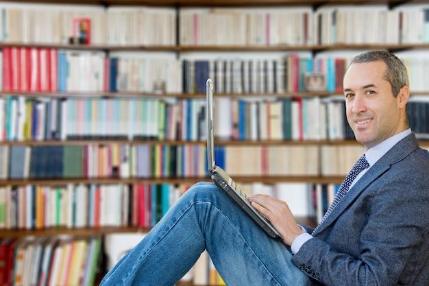 Jonge schrijver zit een boekenkast, met een laptop