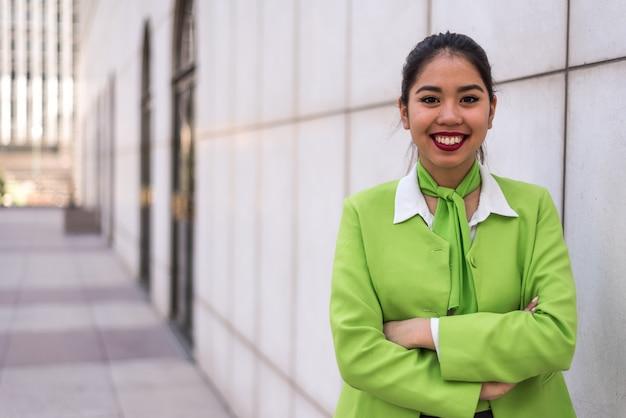 Jonge scortvrouw of bemanning die gekruiste wapens groen glimlachen