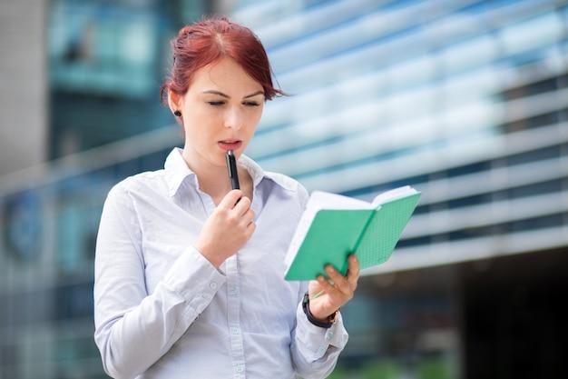 Jonge secretaresse die haar agenda leest openlucht