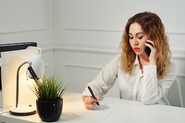 Jonge secretaresse met krullend haar praat op de mobiele telefoon met de klant en maakt aantekeningen aan tafel op kantoor. kantoor werkconcept.