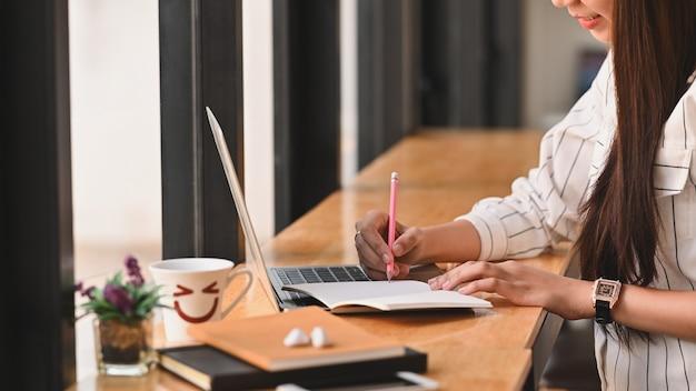 Jonge secretaris vrouw in wit gestreept shirt zit aan de houten bureau en schrijven op de notebook
