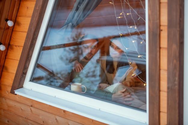 Jonge serene aanhankelijk paar in truien kijken door groot raam van landhuis op winterweekend terwijl u geniet van rust