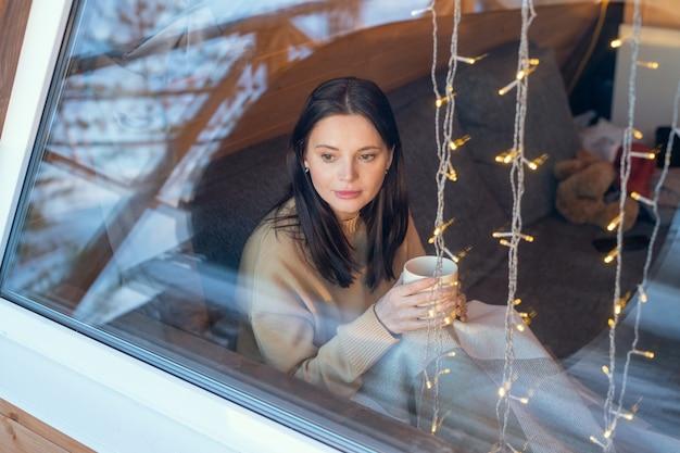 Jonge serene brunette vrouw in trui met hete thee terwijl ze op de bank zit bij het grote raam van het landhuis in het winterweekend