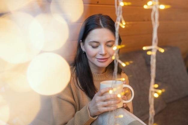 Jonge serene brunette vrouw met mok hete thee zittend op de bank bij een groot raam van het landhuis in het winterweekend en genietend van rust