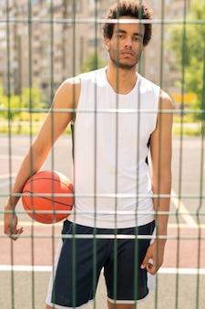 Jonge serieuze actieve speler met bal op zoek naar je door hek van basketbalveld of speeltuin na wedstrijd