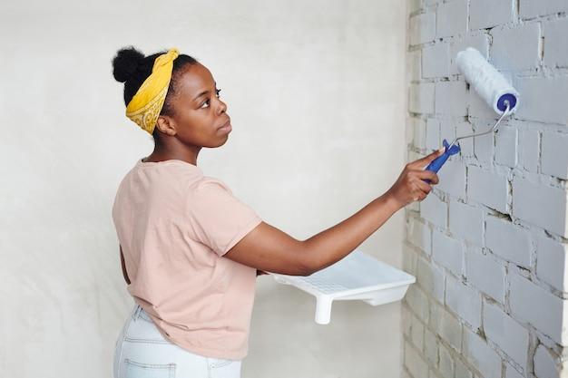 Jonge serieuze afrikaanse vrouw met verfroller die in de hoek voor de bakstenen muur van de woonkamer staat terwijl ze deze in witte kleur schildert