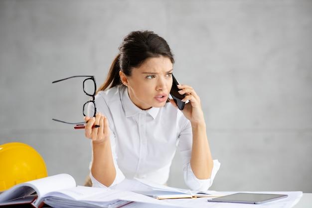 Jonge serieuze architect die op het bureau leunt en een belangrijk telefoongesprek met investeerders heeft.