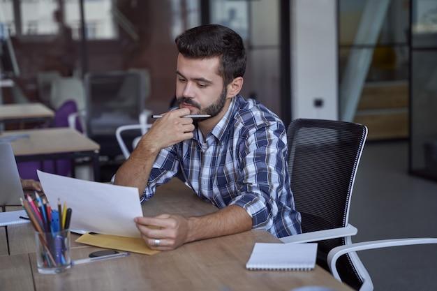 Jonge serieuze blanke zakenman of mannelijke kantoormedewerker die een document analyseert op het werk zittend