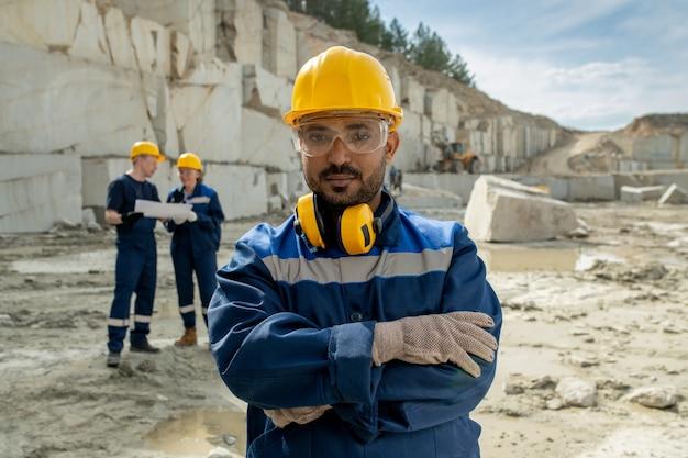 Jonge serieuze bouwer in werkkleding die op de werkplek staat