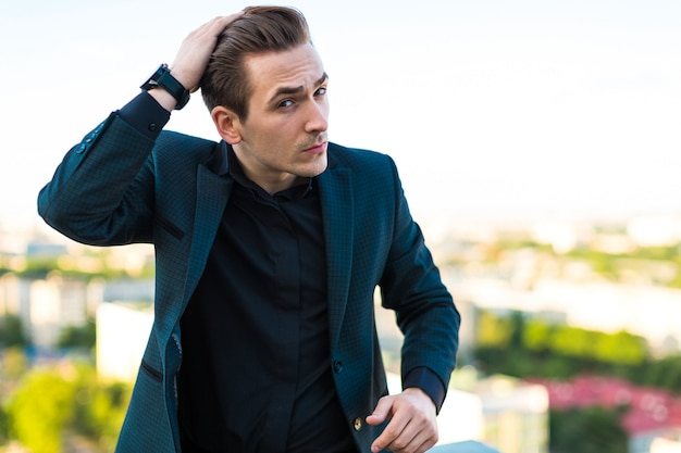 Jonge serieuze busunessman in donker pak, horloge en zwart shirt staan op het dak