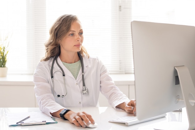 Jonge serieuze clinicus in witte jas die door de gegevens van haar patiënten kijkt terwijl ze voor een computermonitor zit op de werkplek in het ziekenhuis
