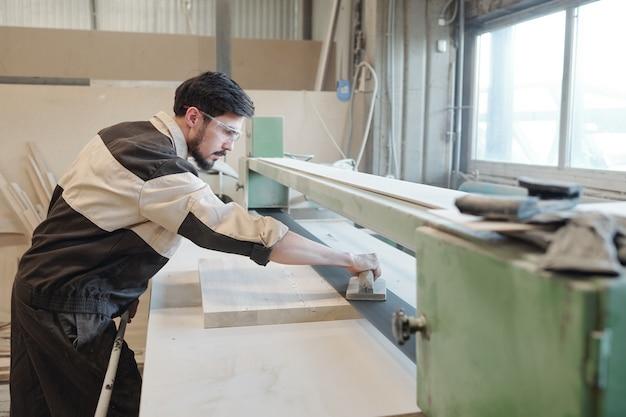 Jonge serieuze fabrieksarbeider die mechanisch handgereedschap gebruikt om het oppervlak van een houten plank of werkstuk glad te strijken terwijl hij over de werkbank buigt