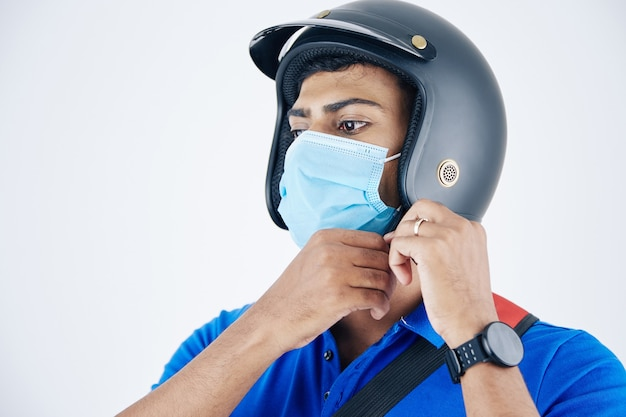 Jonge serieuze indiase koerier in beschermend masker die helm vastmaakt en zich klaarmaakt om voet aan klant te leveren