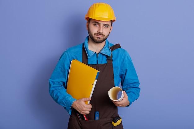Jonge serieuze ingenieur met papieren mappen in handen, camera kijken met zelfverzekerde gezichtsuitdrukking, helm en schort dragen