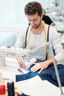 Jonge serieuze kleermaker te concentreren op het naaien werk zittend door de machine in de werkplaats en afronden met bestelling