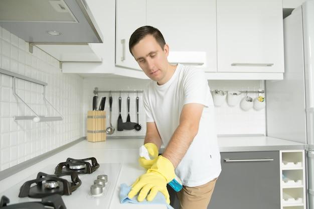 Jonge serieuze man met rubberen geel handschoenen die de stoof schoonmaken