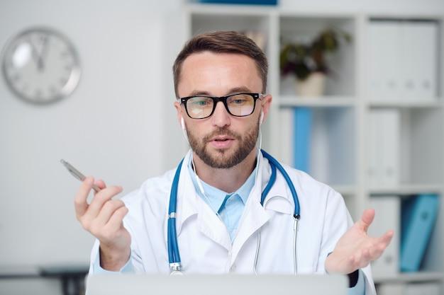 Jonge serieuze mannelijke arts in witte jas, bril en oortelefoon die medische aanbevelingen geeft aan online patiënt terwijl hij naar het scherm van de laptop kijkt