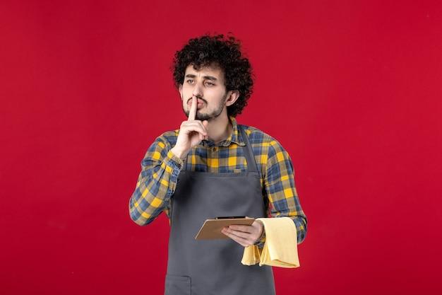 Jonge serieuze mannelijke server met krullend haar die een handdoek vasthoudt die de bestelling opneemt en stiltegebaar maakt op geïsoleerde rode achtergrond