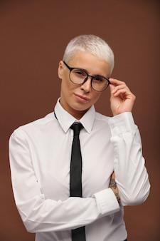 Jonge serieuze mannelijke vrouw in formele kleding die haar bril aanraakt terwijl ze zich een beetje opzij buigt en je geïsoleerd aankijkt