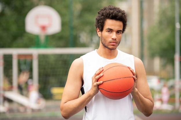 Jonge serieuze multiculturele atleet die bal houdt voor het spelen van basketbal terwijl hij staat