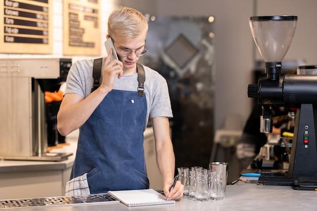Jonge serieuze ober of barista van café die de volgorde van de klant opschrijft tijdens het praten op de mobiele telefoon door zijn werkplek