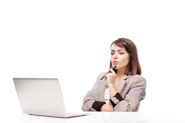 Jonge serieuze officemanager of andere werknemer kijken naar online video op laptopvertoning tijdens het werk