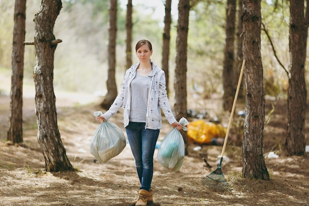 Jonge serieuze vrouw in vrijetijdskleding met vuilniszakken die afval in een bezaaid park of bos schoonmaken. probleem van milieuvervuiling