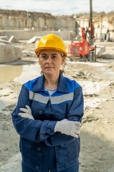 Jonge serieuze vrouwelijke bouwer in werkkleding die op de bouwplaats staat