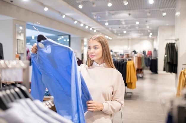 Jonge serieuze vrouwelijke shopper met hanger met blauw shirt tijdens het kijken door nieuwe collectie of vrijetijdskleding op seizoensuitverkoop