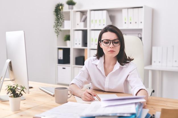 Jonge serieuze zakenvrouw financieel papier kijken tijdens het maken van aantekeningen in notitieblok tijdens analyse van de situatie in de markt