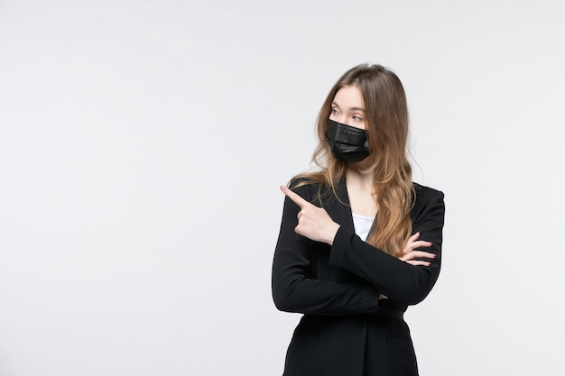 Jonge serieuze zakenvrouw in pak met een medisch masker en iemand aan de rechterkant wijzend op een geïsoleerde witte muur