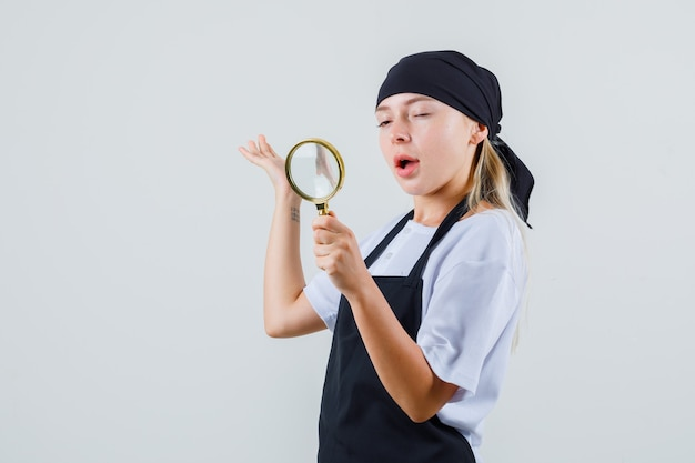 Jonge serveerster die door vergrootglas en oog in uniform en schort kijkt