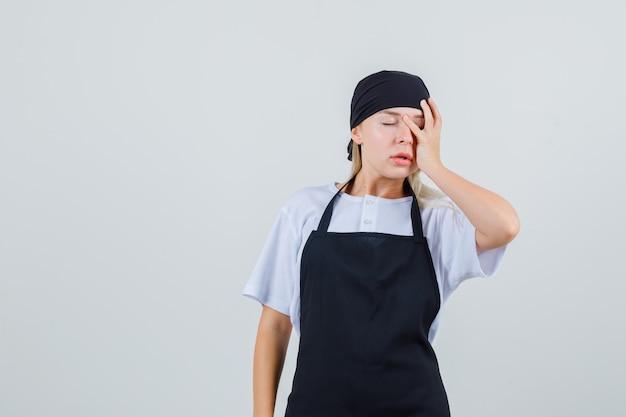 Jonge serveerster die hand op gezicht in uniform en schort houdt en vergeetachtig kijkt
