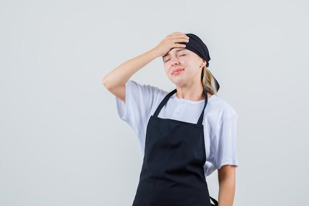 Jonge serveerster die hand op voorhoofd in uniform en schort houdt en vergeetachtig kijkt