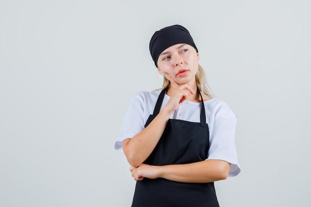 Jonge serveerster die vinger op wang in uniform en schort houdt en peinzend kijkt