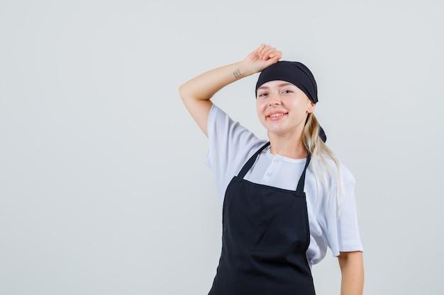 Jonge serveerster die vuist op hoofd in uniform en schort houdt en er vrolijk uitziet