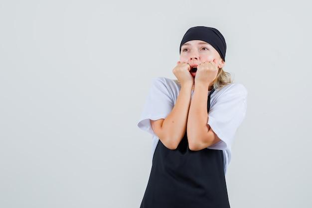 Jonge serveerster die vuisten dichtbij mond in uniform en schort houdt en bang kijkt