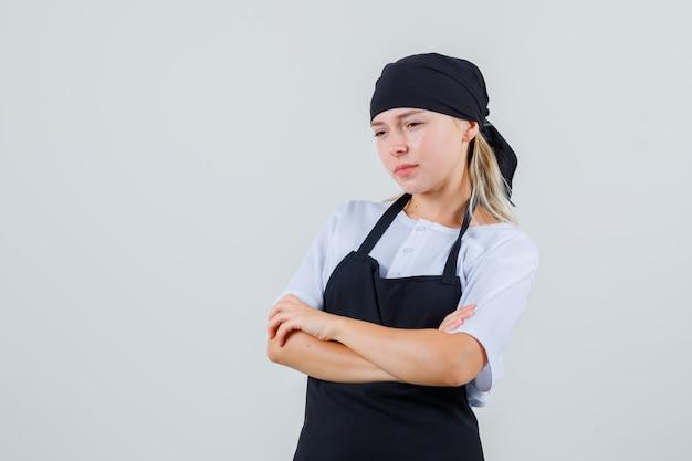 Jonge serveerster die zich met gekruiste armen in uniform en schort bevindt en verdrietig kijkt