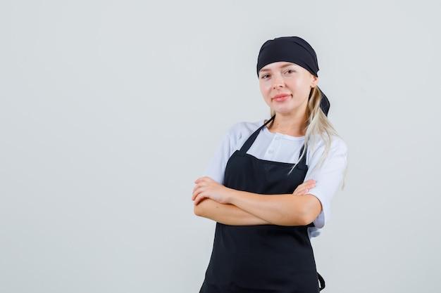 Jonge serveerster die zich met gekruiste armen in uniform en schort bevindt en vrolijk kijkt