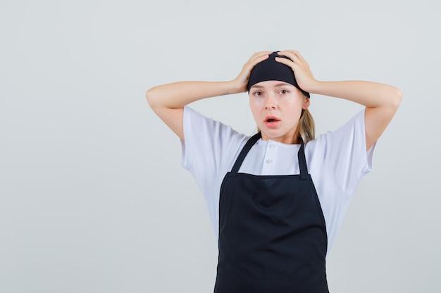 Jonge serveerster hand in hand op het hoofd in uniform en schort en verbaasd op zoek