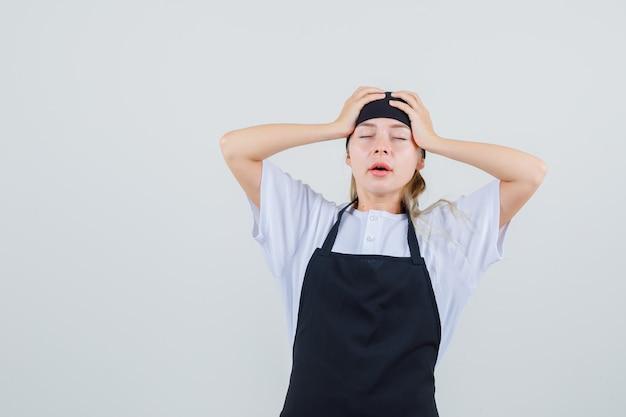 Jonge serveerster hand in hand op het hoofd in uniform en schort en ziet er moe uit