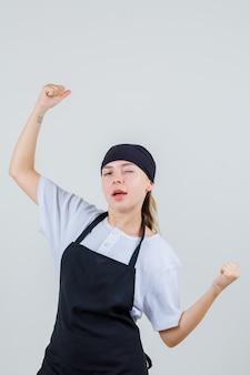 Jonge serveerster in uniform en schort die winnaargebaar toont en er zelfverzekerd uitziet