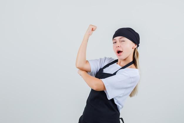 Jonge serveerster in uniform en schort met spier- en knipoogoog en op zoek zelfverzekerd