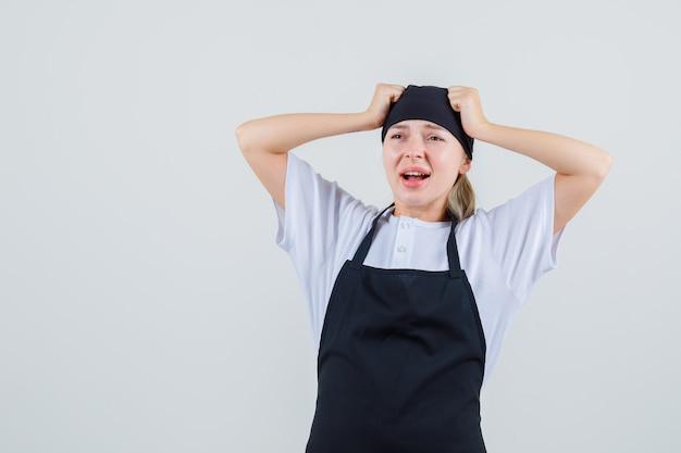 Jonge serveerster in uniform en schort met vuisten op het hoofd en op zoek triest
