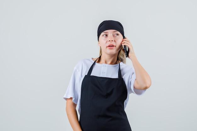 Jonge serveerster in uniform en schort wegkijken tijdens het gesprek op de mobiele telefoon