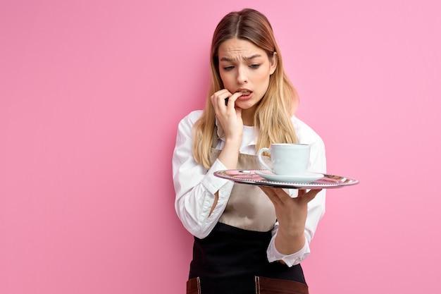 Jonge serveerster met dienblad in handen, bevindt zich bezorgd over iets dat op roze studioachtergrond wordt geïsoleerd.