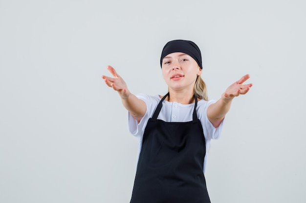 Jonge serveerster nodigt uit om in uniform en schort te komen en ziet er vrolijk uit