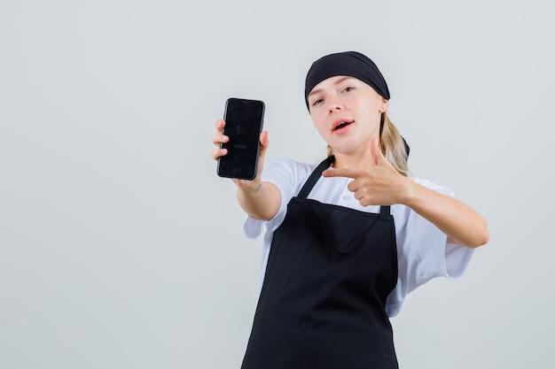 Jonge serveerster wijzend op mobiele telefoon in uniform en schort en kijkt zelfverzekerd