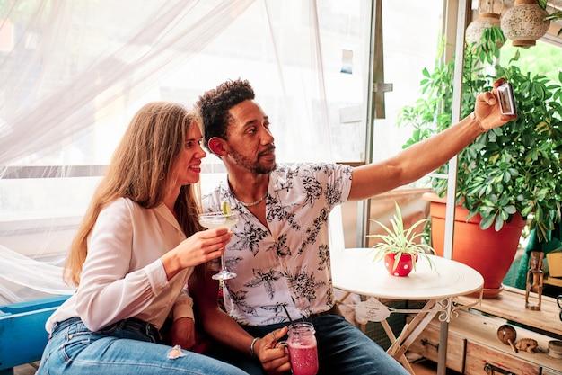 Jonge sex tussen verschillendre rassen paar verliefd selfie te nemen aan de bar